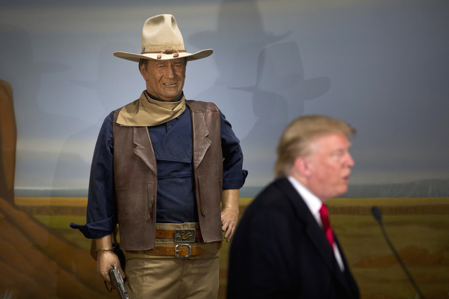 Republican presidential candidate Donald Trump stands in front of a wax statue of John Wayne during a news conference at the John Wayne Museum, Tuesday, Jan. 19, 2016, in Winterset, Iowa. (AP Photo/Jae C. Hong)