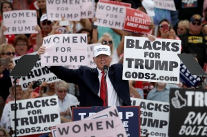 Republican U.S. presidential nominee Donald Trump holds up signs at the end of a campaign rally in Lakeland